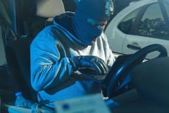 Car theft. A thief stealing a car and starting it with a lap top royalty free stock photos