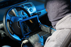 Car theft. Car thief stealing a car. Starting he car with a lap top code breaker Royalty Free Stock Photography