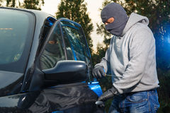 Car theft. Car thief successfully breaking into a car on the parking lot royalty free stock image