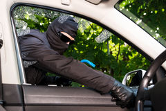 Car theft. Thief successfully breaking a vehicle's window stock photography