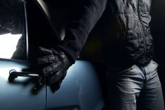 Car thief. Thief in black glowes stealing blue car Royalty Free Stock Photos