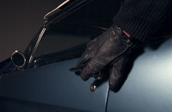 Car thief. Thief in black glowes stealing blue car Stock Photo