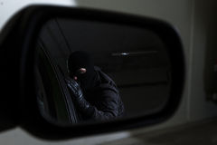 Car thief. Man showing in reflection in car mirror Stock Image