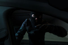 Car thief. Man wearing a black mask reaching throug car window Royalty Free Stock Image