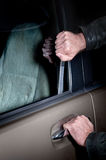 Car thief. A car thief uses a Slim Jim tool to pop the lock on a car door to steal it Stock Images