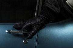Car thief. Man trying to steal blue car Stock Photo