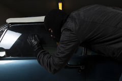 Car thief. Man trying to steal blue car Stock Photos