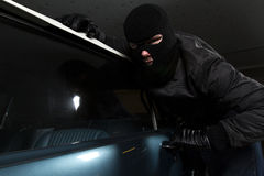Car thief. Man trying to steal blue car Royalty Free Stock Image