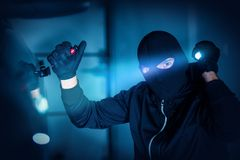 Car Thief Car Robbery. Concept Photo. Caucasian Male Thief in Black Mask Trying to Open Car Using Custom Tool and Flashlight. Car Robber Stock Photography