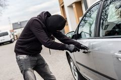 Car thief, car theft. The man dressed in black with a balaclava on his head trying to break into the car. He uses a screwdriver. Car thief, car theft concept stock images