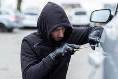 Car thief, car theft. The man dressed in black with a hood on his head trying to break into the car. Car thief, car theft concept Stock Image