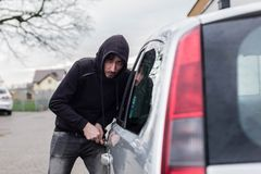 Car thief, car theft. The man dressed in black with a hood on his head trying to break into the car. Car thief, car theft concept royalty free stock photos