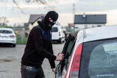 Car thief entering the vehicle and stealing a car. Stock Photography
