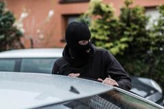 Car thief entering the vehicle and stealing a car. Royalty Free Stock Images