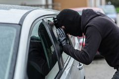 Car thief looking through car window Stock Image