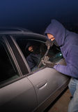 Car thief looking to open a locked vehicle Royalty Free Stock Photo