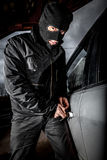 Car thief in a mask. Robber and the car thief in a mask opens the door of the car and hijacks the car Royalty Free Stock Images