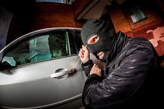 Car thief in a mask. Robber and the car thief in a mask opens the door of the car and hijacks the car Royalty Free Stock Photos