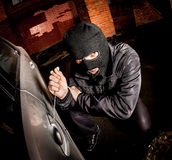 Car thief in a mask. Robber and the car thief in a mask opens the door of the car and hijacks the car Stock Photo