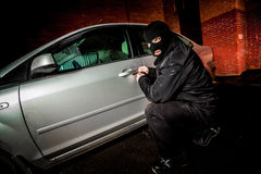 Car thief in a mask. Robber and the car thief in a mask opens the door of the car and hijacks the car Royalty Free Stock Image