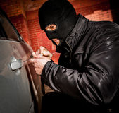 Car thief in a mask. Robber and the car thief in a mask opens the door of the car and hijacks the car Stock Image