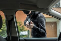 Car thief pointing a gun at the driver Stock Images