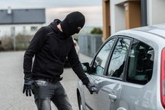 Car thief pulls the handle of a car. Man dressed in black with a balaclava on his head pulls the handle of a car. Car thief, car theft concept Royalty Free Stock Photos