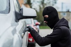 Car thief pulls the handle of a car. Royalty Free Stock Photos