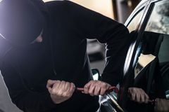 Car Thief tries to break into car with crowbar Royalty Free Stock Image