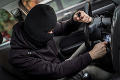 Car Thief tries to start the car. With a screwdriver in the ignition. Car thief, car theft Stock Photography