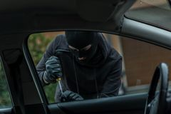 Car thief trying to break into the car. The man dressed in black with a balaclava on his head trying to break into the car. He uses a screwdriver. Car thief, car Royalty Free Stock Photos