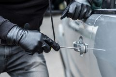 Car thief trying to break into a car with a screwdriver. Car thief, car theft Royalty Free Stock Photos