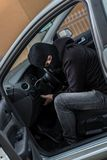 Car thief trying to run a car. Man dressed in black with a balaclava on his head trying to run a car. Car thief, car theft concept Stock Image