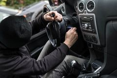 Car thief trying to run a car. Man dressed in black with a balaclava on his head trying to run a car. Car thief, car theft concept Stock Photo