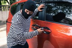Car thief trying to unlock a car by remote control, Thief and ro. Car thief trying to unlock a car by remote control., Thief and robbery concept Stock Photos