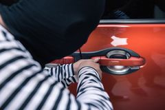Car thief trying to unlock a car by screwdriver.  Stock Image