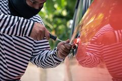 Car thief trying to unlock a car by screwdriver.  Stock Photo