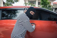 Car thief trying to unlock a car by screwdriver.  Stock Images