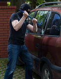 Car thief using crowbar Royalty Free Stock Photos