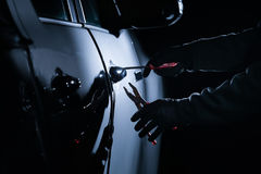 Car thief using a tool to break into a car royalty free stock image