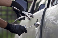 Car thief using a tool to break into a car. Stock Images