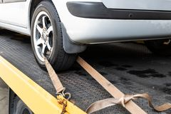 Car tied with security strap on flatbed tow truck. Broken down car tied with security strap on flatbed tow truck for transport to workshop garage to repair stock photos
