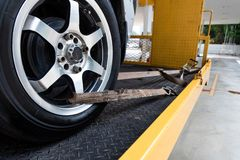 Car tied with security strap on flatbed tow truck. Broken down car tied with security strap on flatbed tow truck for transport to workshop garage to repair royalty free stock images