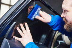 Car tinting. Automobile mechanic technician applying foil. On window in repair garage workshop Stock Photo