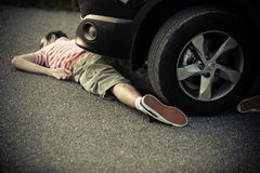 Car tire and bumper over unconscious boy Stock Photos
