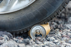 Car tire on can. Tire drove on can and deformed it Royalty Free Stock Photos