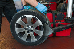 Car tire changing. Car mechanic changing a tire royalty free stock image