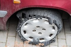 Car tire completely damaged after leak and continue driving. Tire blowout defect failure.  Stock Photography