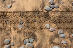 Car tire footpring in a sand stones beach Stock Image
