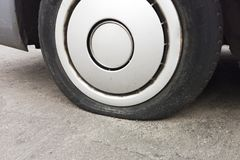 Car tire leak because of nail pounding. Flat tyre on road. Flatten punctured auto wheel. Damaged flat tire of a car on the road.  stock photos